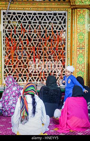 boy and prayers, in Hazrat Nizamuddin Dargah, Delhi, India - Stock Photo