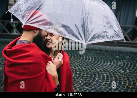 guy and girl under an umbrella - Stock Photo