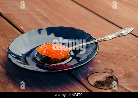 red caviar in a blue plate. wood planks - Stock Photo