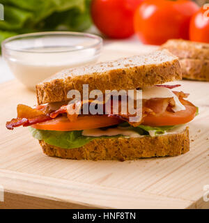 tasty bacon sandwich on wooden table with mayonnaise - Stock Photo
