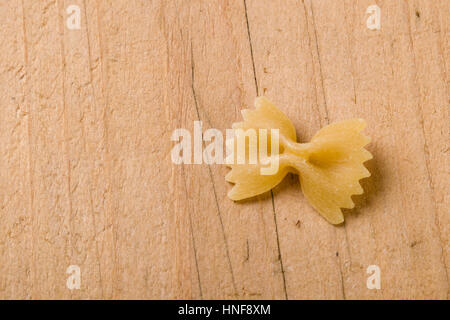 raw farfalle bow-tie pasta on wooden table - Stock Photo