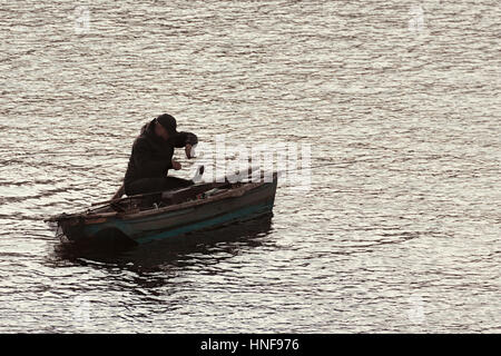 Prague, Czech Republic - October 15, 2016: fisherman enjoying his hobby on a small traditional vintage boat on river - Stock Photo