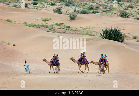 Tourists riding camels on Sam dunes in Desert National Park in the Great Thar Desert,near Jaisalmer, Rajasthan, - Stock Photo