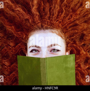 Young redhead woman reading a book - Stock Photo
