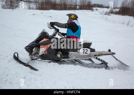 A sportsman takes part in the Volga Cup on snowmobile sport during the Winter Sports Festival in Uglich, Russia - Stock Photo
