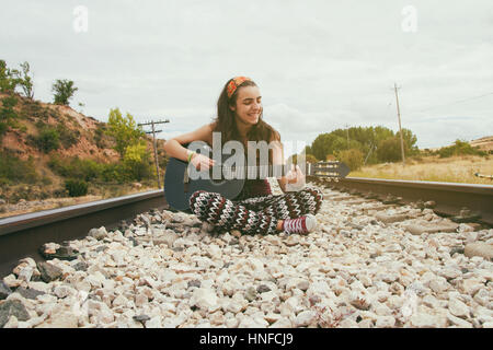 Teen woman in a railroad way with her guitar - Stock Photo