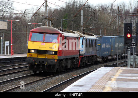 Class 90 electric locomotives with a container train passing through Lancaster station on the West Coast Main Line - Stock Photo