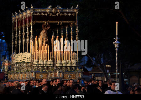 A Christian brotherhood carrying a float during the Holy Week (Semana Santa) celebrations in Malaga, Spain - Stock Photo