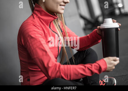 Calm smiling girl sits on the floor in the gym next to the gray wall. She holds a black cup in the hands. Woman - Stock Photo