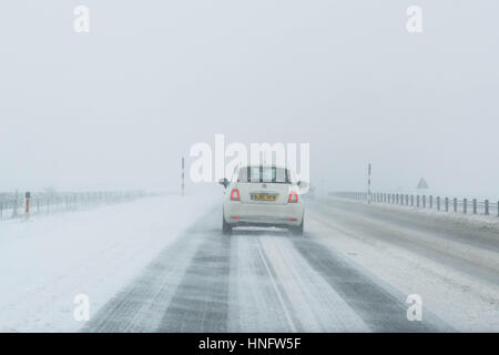 white car driving on A66 road in Northern England in winter in drifting snow - Stock Photo