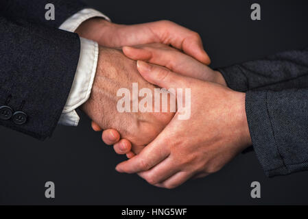 Businessman and businesswoman handshake in office, people greeting each other at business meeting, close up of hands - Stock Photo