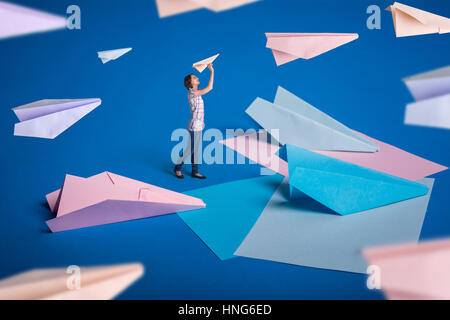Creative surrealism design with origami paper planes. Young girl let paper airplanes. Blue, blue, pink origami crafts. - Stock Photo
