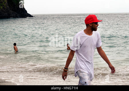 Cool Dude Strolls Along Sandy Beach in Bali Indonesia Wearing Red Baseball Hat, White T-Shirt and Short Pants - Stock Photo