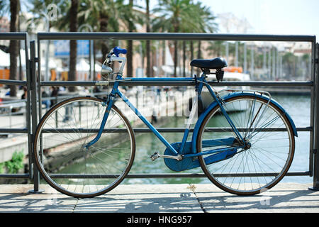 Blue bicycle near railing on a bridge over sea - Stock Photo