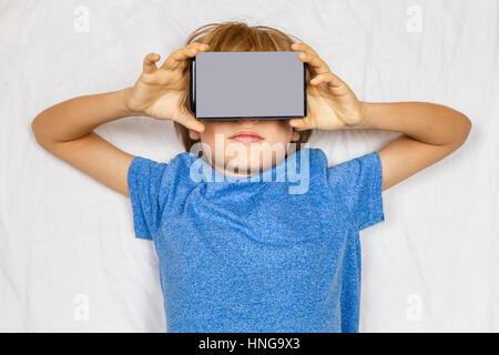 Child liying on bed with 3D VR cardboard glasses. Toned image - Stock Photo