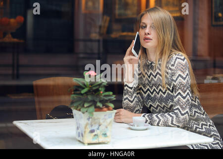 Beautiful woman calling with her smartphone. City cafe - Stock Photo