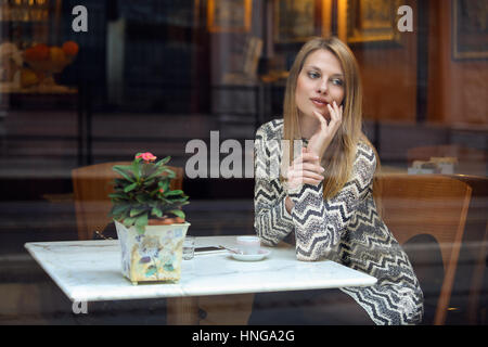 Elegant young woman in a classy cafe. Urban shot - Stock Photo