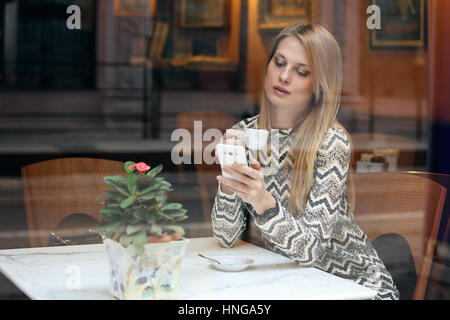 Beautiful girl using her mobile phone in cafe. City lifestyle - Stock Photo