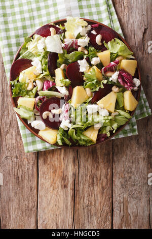 Healthy food: salad of beets, pineapple, goat cheese and greens mix closeup on a plate. vertical view from above - Stock Photo