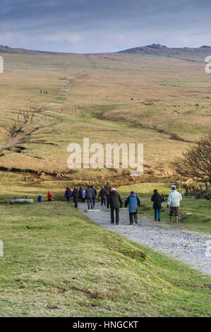 A group of walkers on Rough Tor, designated as an area of Outstanding Natural Beauty on Bodmin Moor in Cornwall. - Stock Photo