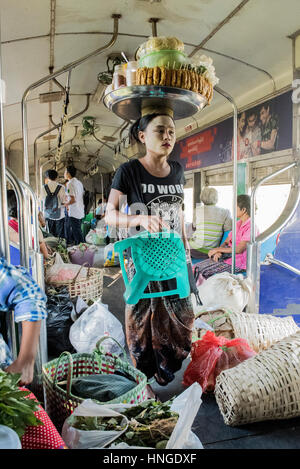 Burmese woman selling food on a train with her produce balanced on her head as she walks through a crowded carriage - Stock Photo