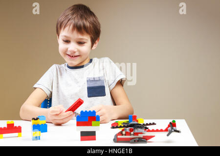 Smiling little kid playing with colorful plastic construction bricks at home - Stock Photo