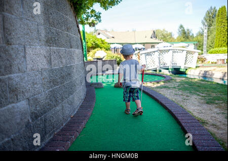 Little boy preschooler playing mini-golf or crazy golf at a mini-golf course in summer - Stock Photo