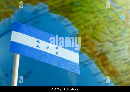 Honduras flag with a globe map as a background macro - Stock Photo