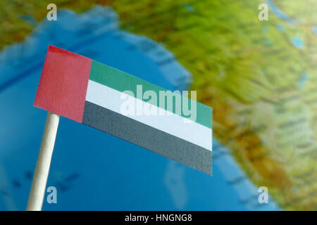 United Arab Emirates flag with a globe map as a background macro - Stock Photo