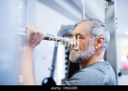 Senior man in gym doing pull-ups on horizontal bar. - Stock Photo