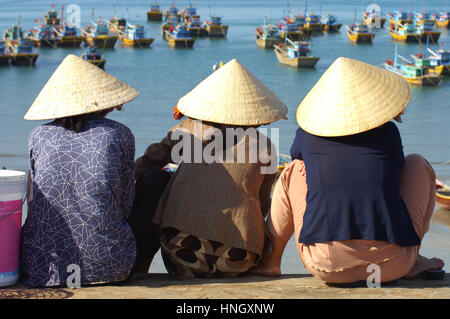 MUI NE, VIETNAM - FEB 2005 : Three women in conical hats wait at the harbourside for the morning catch, Mui Ne, - Stock Photo