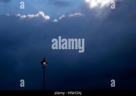 A iluminated street light set against a dark stormy sky. - Stock Photo