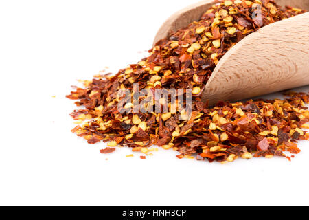 The pile of a crushed red pepper, dried chili flakes and seeds isolated on white background in a scoop - Stock Photo