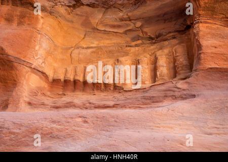 Symbols hewn in canyon Siq, passage leading to ancient city of Petra, Jordan - Stock Photo