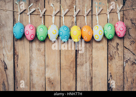 Colorful easter egg hanging on wood background - Stock Photo