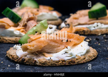 Salmon and cucumber canapes on oat cakes with black cracked pepper - Stock Photo