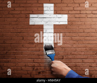 People hand with paint brush making white cross shape on brick wall - Stock Photo