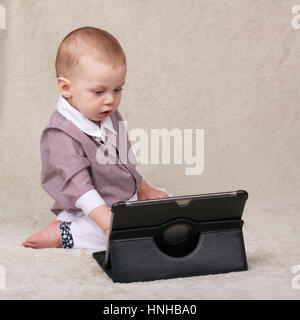 Baby busy using an electronic tablet while sitting on blanket - Stock Photo