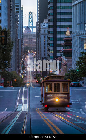Classic view of historic Cable Car riding on famous California Street in beautiful early morning twilight before - Stock Photo