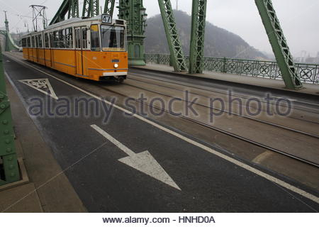A yellow tram crosses Liberty Bridge in Budapest, Hungary on a foggy day. - Stock Photo