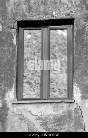 Single window closeup in a cracked wall - Stock Photo