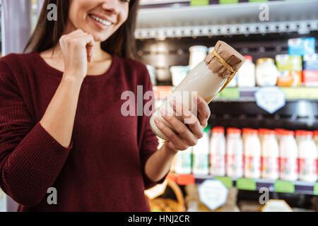 Happy beautiful young woman choosing and buying yogurt in grocery shop - Stock Photo