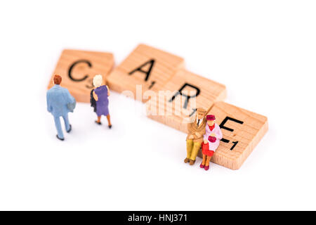Scrabble letters make up the word CARE. An elderly couple sit on the letter E of the word CARE as a younger couple - Stock Photo