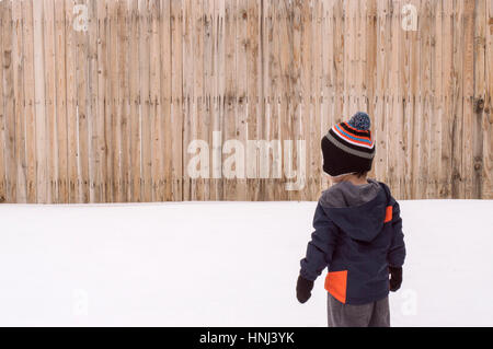 Rear view of boy standing on snow covered field against fence - Stock Photo