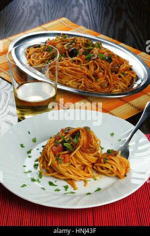 Spaghetti puttanesca on colorful placemats lying on wooden table - Italian recipe with garlic, olive oil, anchovies, - Stock Photo