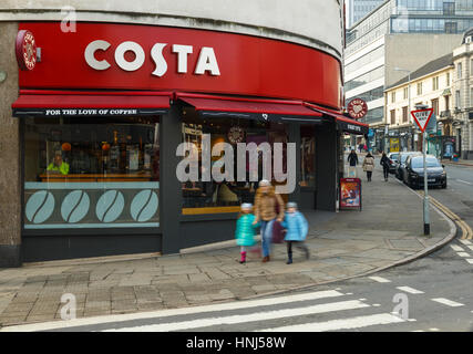 NOTTINGHAM, ENGLAND - FEBRUARY 13: Woman with two children (motion blur) walking past Costa coffee, Nottingham. - Stock Photo