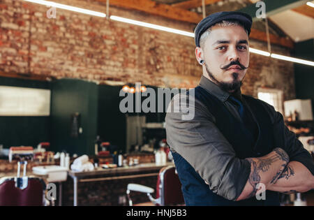 Portrait of serious looking young man standing with his arms crossed at barber shop. Male hairdresser standing in - Stock Photo