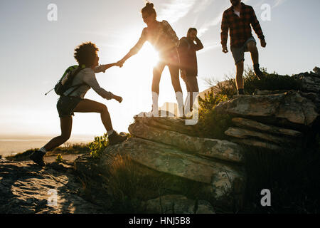 Group of hikers on a mountain. Woman helping her friend to climb a rock. Young people on mountain hike at sunset. - Stock Photo