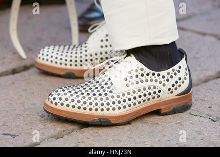 Man with white leather shoes with studs before Salvatore Ferragamo fashion show, Milan Fashion Week street style - Stock Photo