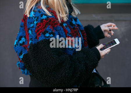 Woman with black, red and blue fur coat before Etro fashion show, Milan Fashion Week street style on January 16, - Stock Photo
